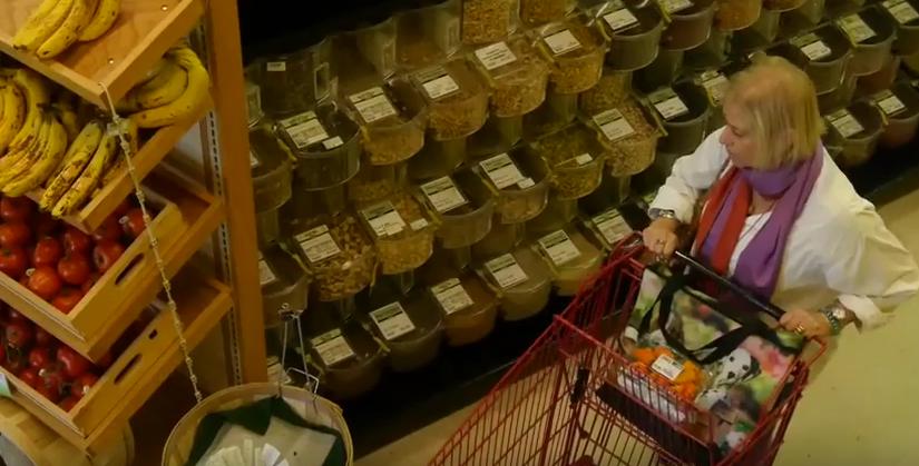 Women pushing cart in health food store